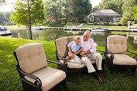 Portrait of father hugging son on sofa in backyard with view of lake