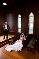 Young interracial bride and groom posing in wooden church on wedding day