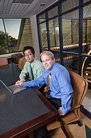 Portrait of two multi_ethnic businessmen sitting with laptop in boardroom