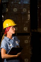 Femaie worker wearing hard hat standing in storage warehouse