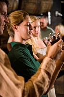 Group of people examining wine at a winery tour and tasting