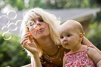Close_up of mother blowing bubble wand with baby looking