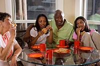 Portrait of parents/grandparents and teenage daughters eating cookies at dining table