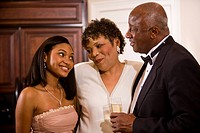 African American teenage girl in formal attire standing with parents/grandparents