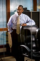Mature African American businessman standing in conference room leaning on chair