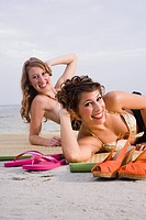 Portrait of young women lying on mats on beach
