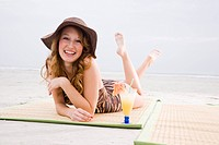 Portrait of attractive young woman lying on mat on beach enjoying tropical drink