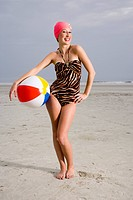 Young woman holding beach ball