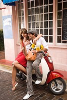 Portrait of young couple sitting on motor scooter parked outside store