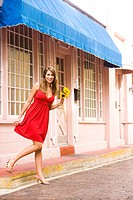 Young woman in sexy red dress holding flowers stepping off curb outside shop