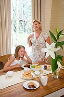 Portrait of grandmother standing beside granddaughter at breakfast table