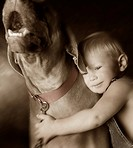 Child embracing dog
