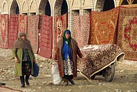 Two women carpet sellers with carpets displayed on ropes in the Urgut Bazaar in Uzbekistan, Central Asia, Asia