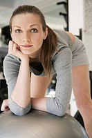 Portrait of young woman leaning to fitness ball