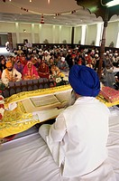 Sikh priest and holy book at Sikh wedding, London, England, United Kingdom, Europe