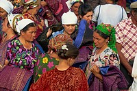 Women in bright dresses and head scarves in the new clothes market within the Old City wall of Bukhara, Uzbekistan, Central Asia, Asia
