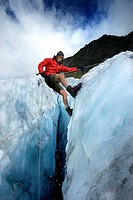 Mountain guide abseiling in glacier crevasse