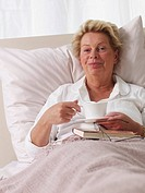 senior lady having a cup of coffee in bed