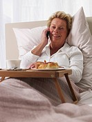 elderly lady with her mobile in bed