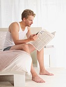 young man reading news on the bed