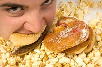 Close up of a young male eating a hamburger and jam donut with popcorn to follow.