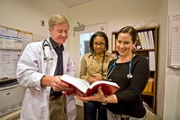 A woman resident physician (center) confers with two staff doctors before making clinic rounds at Childrens Hospital of Orange County in Orange, Calif...