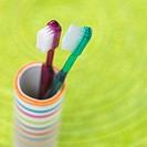 two toothbrushes in a striped beaker