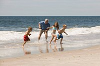 Grandfather and grandchildren playing on beach