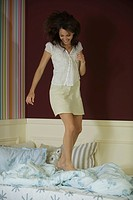 Young woman jumping on bed, full length
