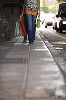 Woman walking on sidewalk, carrying shopping bags, low angle view