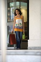 Young woman exiting store with shopping bags, smiling