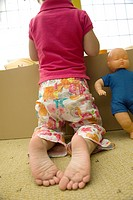 Little girl kneeling before box of toys, rear view