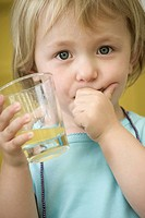 Toddler girl holding glass of juice, covering mouth with one hand