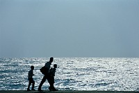 Man walking with two sons, silhouetted against ocean