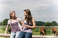 portrait of two girls sharing a laugh on horse ranch