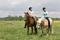 two girls doing horseback riding