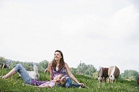 full body portrait of two girls sitting on meadow at horse ranch