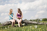 two girls sitting together on tree trunk at horse ranch