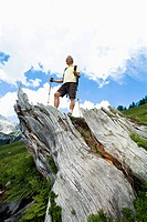low angle view of mature man standing on log in the mountains