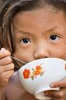 Little street waif eats rice, Phnom Penh, Cambodia No model release available