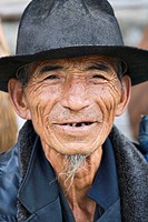 Hat, smile, and whiskers: a senior, Hani miniroty man at Shalatou market, Yuanyang, Yunnan, China No model release available