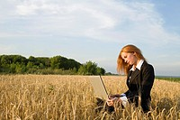 Businesswoman with a Laptop in a Field