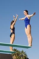 Two women standing on diving boards