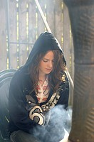 Girl sitting beside fire wearing a hoody