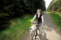 30 Something woman cycling through forest with dog running alongside her