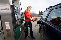 Young woman pumps gas into a car at a gas station in Homer, Alaska
