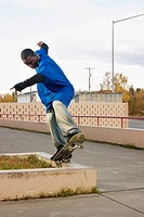 Male skateboarder doing trick on concrete curb