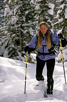 Woman snowshoeing in forest USA