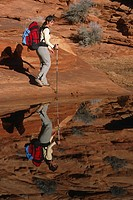 Woman backpacking along pond in Utah USA