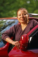 Portrait of Hispanic woman with car Summer USA